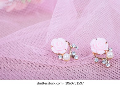 Beautiful earrings with flowers on a pink background