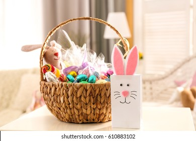 Beautiful Easter basket and cute gift bag on white table