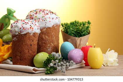 Beautiful Easter cakes, colorful eggs and candles on wooden table on yellow background