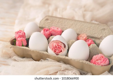 beautiful Easter still life. cute eggs in  cardboard box and rose flowers. decoration of Easter food. spring season. soft selective focus