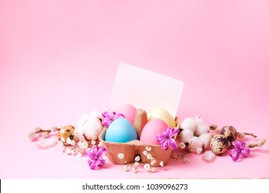 Beautiful easter table setting festive composition. Four color eggs in carton w/ purple flowers on pink table background w/ blank greeting card. Minimalistic holiday scene. Top view, copy space.