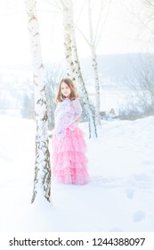 A beautiful eight years old girl walks on a frozen forest covered with snow.