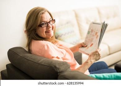 Beautiful elder granny with newspaper between her hands spending time in the living room