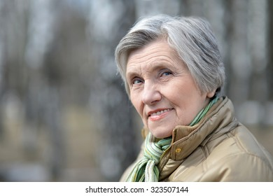 beautiful elder woman on a walk outdoors in spring