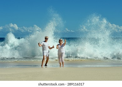 Beautiful elderly couple standing on the beach