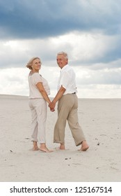 Beautiful elderly couple went to the beach to enjoy the sea breeze