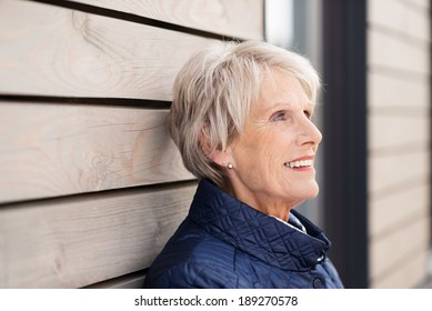 Beautiful elderly lady standing leaning against a wooden building reminiscing with a nostalgic expression on her face