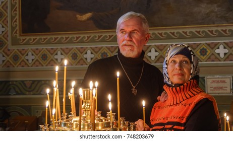 Beautiful elderly married couple with gray hair with candles in orthodox church