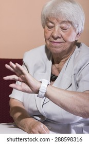 Beautiful elderly woman checking the time looking at her wrist watch as she relaxes on a sofa in her living room