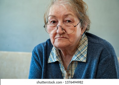 Beautiful elderly woman with gray hair in red glasses with wrinkled face. Retired waiting for guests. Social assistance, care for sick and elderly