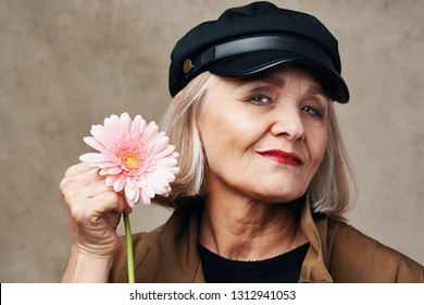 beautiful elderly woman  with a hat holding a pink flower in her hand on March 8 holiday women's day