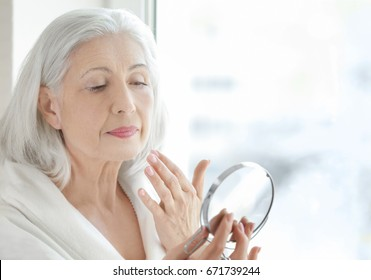 Beautiful elderly woman holding mirror and applying face cream at home