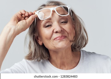 Beautiful elderly woman lifts her glasses on her forehead