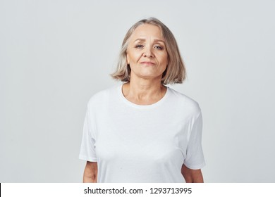 beautiful elderly woman in a light shirt on a gray background looking into the camera, short hair