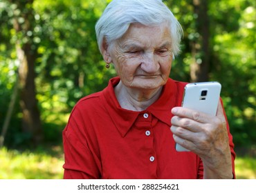 Beautiful elderly woman looking at a smartphone