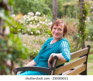 beautiful elderly woman in  park with flowers in spring day