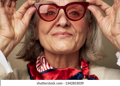 Beautiful elderly woman in sunglasses is smiling at the camera and a red scarf around her neck