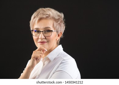 beautiful elderly woman in a white shirt and glasses on a black background
