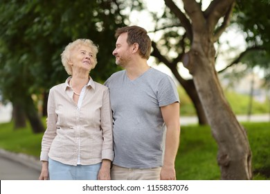 Beautiful eldery woman and her grown ups son together in park. Two generations of family.
