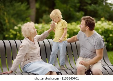 Beautiful eldery woman and her grown ups son, and her little grandson together in park. Three generations of family