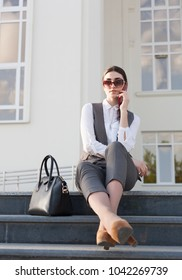 Beautiful elegance lady brunette woman, clothed in gray business suit, white cotton blouse, sunglasses, holding black leather handbag, smart phone. Urban city portrait. Business corporate style.