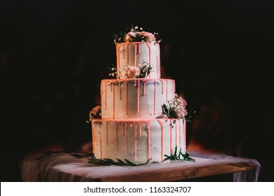 Beautiful elegant big three layers white wedding cake decorated with pink cream and fresh flowers. Cake standing on table isolated at black background. Horizontal color photography.