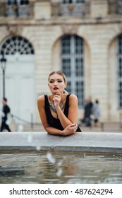 Beautiful elegant blonde poses by a fountain.