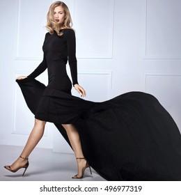 Beautiful elegant blonde woman posing in black maxi dress, looking at camera. Indoor shot.