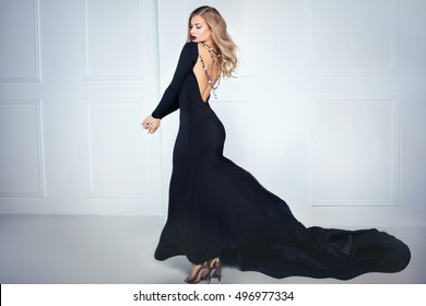 Beautiful elegant blonde woman posing in black maxi dress, back view. Indoor shot.