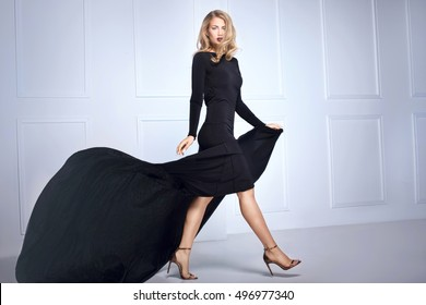 Beautiful elegant blonde woman posing in black maxi dress, looking at camera. Indoor shot.
