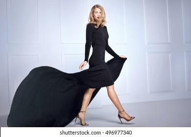 Photo of Beautiful elegant blonde woman posing in black maxi dress, looking at camera. Indoor shot.