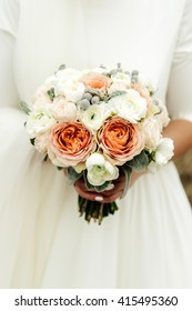 beautiful elegant bride holding and looking at luxury natural wedding bouquet
