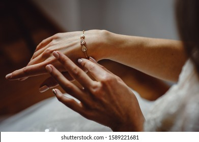 Beautiful elegant bride puts a bracelet on her hand, closeup. Girl put a bracelet on arm.Preparing the bride for the wedding ceremony.