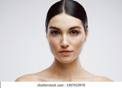 Beautiful elegant brunette with bare shoulders Cosmetology Clean skin Gray background