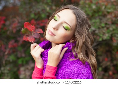 Beautiful elegant brunette girl with perfect hair and a knit scarf purple color and pullover posing on a background of autumn leaves on the bushes.  Early autumn. A series of photos in my portfolio.