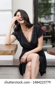 Beautiful elegant brunette girl wearing a black dress with a sexy deep neckline is relaxing in a street cafe. Advertising, fashion, commercial design. Copy space.