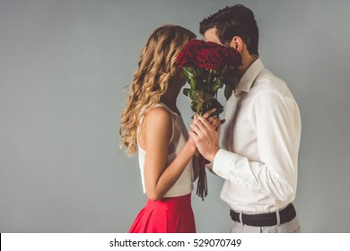 Beautiful elegant couple is kissing behind roses, on gray background