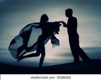 Beautiful elegant couple in love dancing at sunset.