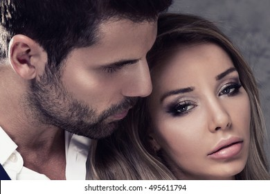 Beautiful elegant couple posing together. Handsome brunette man and blonde sexy woman. Studio shot.