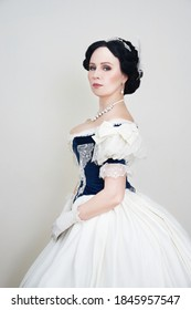 A beautiful elegant dark haired woman in a historic 1867 coronation dress on a white background looks at the camera - Shutterstock ID 1845957547