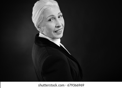 Beautiful elegant elderly woman on dark background, black and white
