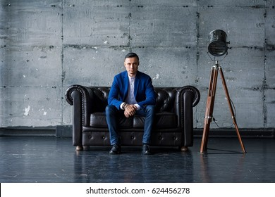 Beautiful elegant fashionable young man in a blue jacket sits on a leather sofa