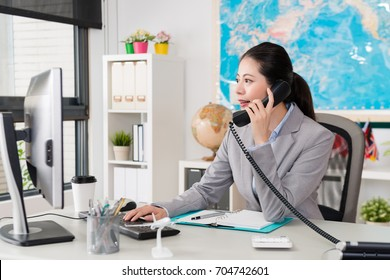 beautiful elegant female office worker looking at computer searching airline ticket status when she using telephone talking with client discussing travel plan.