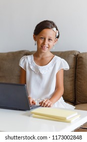 Beautiful, elegant girl 8 years old is engaged in home in an online school.