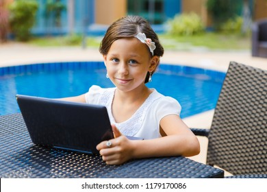 A beautiful, elegant girl of 8 years sitting with a laptop and books outdoors, studying at an online school