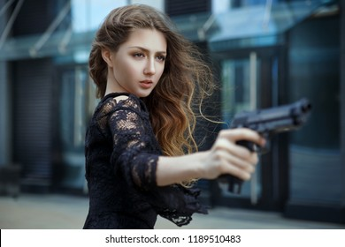 A beautiful elegant girl in an evening dress aims at a  gun.
