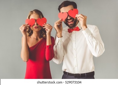 Beautiful elegant girl in red dress and guy in classic shirt and red bow tie are holding paper hearts and smiling, on gray background