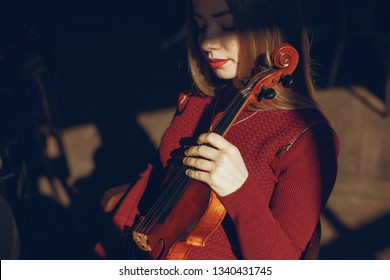 beautiful elegant girl standing in a cafe with violins