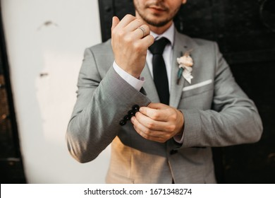 Beautiful elegant groom in wedding suit with long sleeves. Handsome man in tux. Portrait of man wearing glasses in nature. Close up.