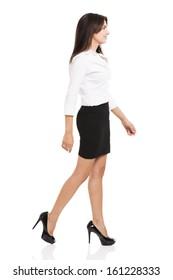 Beautiful and elegant hispanic business woman walking, over a white background